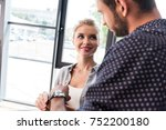 smiling young woman putting on... | Shutterstock . vector #752200180