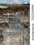 Small photo of Low view of lines of steel rebar in unpoured footings, vertical aspect