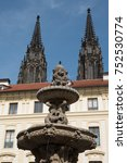 Small photo of Fountain in the courtyard of Prague Castle with St Vitus Cathedral in the background on a sunny day, blue skies. Two spires of St Vitus Cathedral, Prague, Czech Republic.