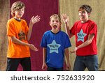 Small photo of Young actor screams as his two friends pose for the camera on either side of him