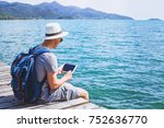 Small photo of traveler using digital tablet computer while sitting on wooden pier, travel app online, man backpacker with wireless device