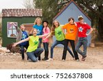 Small photo of Silly group of friends at acting camp pose together in front of stage set