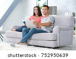 young couple on sofa at home | Shutterstock . vector #752950639