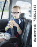 Small photo of Cute boy sitting in a booster seat on a long car ride drinking a smoothie while safely strapped in a car seat. He is wearing his seatbelt and enjoying a drink.