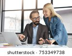 Small photo of Handsome elegant bearded businessman and blonde female office worker stands at work desk, compare figures in notebook with information on laptop, prepare business project, point at diagrams, graphics
