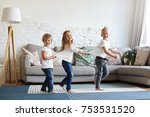 Small photo of Picture of three excited children siblings in white t-shirts and jeansdancing barefooted on wooden floor at home. Two little girls standing in sequence with their blonde elder brother in the lead