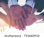 Small photo of Diverse group of people joining hands in supportive gesture. Businessman and businesswomen join hand together as a good support team.