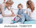 Stock photo teacher talking to a shy boy during classes in kindergarten 753807379