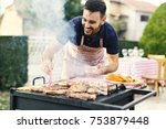 attractive young chef greasing... | Shutterstock . vector #753879448