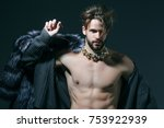 Small photo of Man with fur coat on grey background. Cinderella prince with crown and muscular torso, chest. Freak, gay and transvestite. Drag queen, homosexual and trans. Winter fashion, jewelry, accessory.