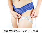 woman measuring thigh with tape | Shutterstock . vector #754027600