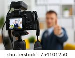 Small photo of Male in suit and tie show confirm sign arm making promo videoblog or photo session in office camcorder to tripod closeup. Vlogger promotion selfie solution or finance advisor management information