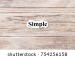 Small photo of Simple of the word on paper. concept. Words of Simple on a wooden background.
