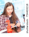 Small photo of Schoolgirl in laboratory robots debug microcontroller