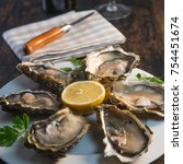 oysters and white wine on wood... | Shutterstock . vector #754451674
