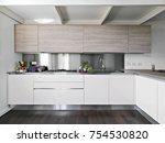 Stock photo interior shots of a modern kitchen in the foreground the steel sink and the cooking hob 754530820