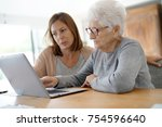 elderly woman using laptop with ... | Shutterstock . vector #754596640