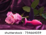 Stock photo silicone dildo sex toy and a pink rose on a dark background 754664059