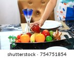 Small photo of Housewife arrange fruit on dinning table