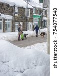 Small photo of WREXHAM, UK - MARCH 22, 2013: Two people walk dogs while it is snowing in a Wrexham village. Walking on the road, unable to use pavements due to the deep snow.