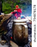 Small photo of Great Bear Rainforest, British Columbia, July 10, 2016: A man in a red coat and toque mends his drysuit while the coffee percolates on the fire in the forground.
