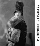 Small photo of Women wearing fur lined velvet coat with opulent fur collar and cuffs. Her 1920s cloche hat is ornamented with ostrich feathers.