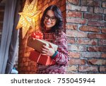 a woman holds christmas gifts. | Shutterstock . vector #755045944