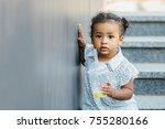 Stock photo black latin cute toddler baby girl put one hand on gray wall and using straw to drink honeydew from 755280166