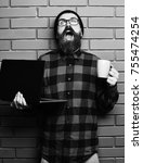 Small photo of Bearded man, long beard. Brutal caucasian happy unshaven hipster holding laptop with mag or cup in red black checkered shirt with hat and glasses on brown brick wall studio background