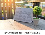 Small photo of Desktop Calendar page 2018 place on a wooden desk at coffee shop,for Planer,organization,management each date,month,year.flower pot .Planer,organization,management Concept.