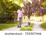 Stock photo senior man walking with pet bulldog in countryside 755507446