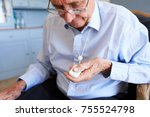 Small photo of Senior Man At Home Using Distress Alarm Call Button