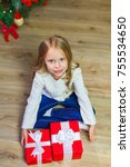 Small photo of Happy little smiling girl with christmas gift box. View from abo