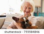 Stock photo senior woman sitting on sofa at home with pet french bulldog 755584846