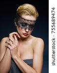 Small photo of Creative portrait of a young woman in a lace mask. Blonde. Studio portrait.
