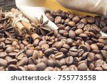 Small photo of Cinnamon sticks wrapped with rope at coffee beans and stars anis about bag on wooden rustic table