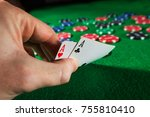 Small photo of Poker chips with two aces on green background.
