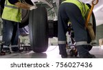 Stock photo airport worker checking chassis engine and chassis of the passenger airplane under heavy 756027436