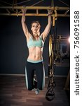 Small photo of Strong fit girl in sportswear doing pull up exercise on horizontal bar. Fitness workout in gym. Muscular young woman.