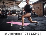 Small photo of Fit young blonde woman in sportswear working out alone in a gym doing core exercises with a swiss ball