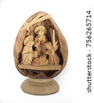 Small photo of tiny wood carved traditional christmas adoration scene inside a nutshell