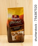 Small photo of RIVER FALLS,WISCONSIN-NOVEMBER 15,2017: A bag of Folgers brand caramel drizzle ground coffee with a wood background.