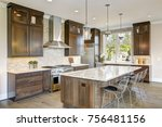 Stock photo luxury kitchen accented with large granite kitchen island taupe tile backsplash natural brown 756481156