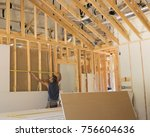 Construction Worker is measuring a wall to sheetrock it. - stock photo