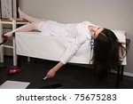Lifeless young nurse with syringe lying on the sofa - stock photo