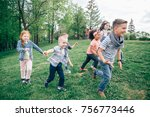 Small photo of A multicultural group of children running on the grass holding hands. The concept of childhood, friendship, intercultural communication. Full length