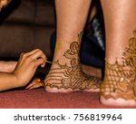 Small photo of Back of left heel and foot of Indian bride having henna paste applied as part of mehndi ceremony, two days before her wedding.The intricate design takes time to apply, dry and become deep, rich stain.