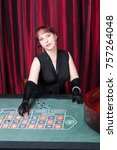 Small photo of ludomania, lass wearing black gloves and black dress parlays in a casino