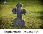 Small photo of Old, stone, tombstone cross on a background of green grass.