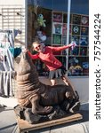 Small photo of OCTOBER 20 2017 - SAN FRANCISCO, CALIFORNIA: Adult female poses next to a giant sea lion wooden statue outside of a Fisherman's Wharf gift shop, acting silly, goofy and childish while on vacation.
